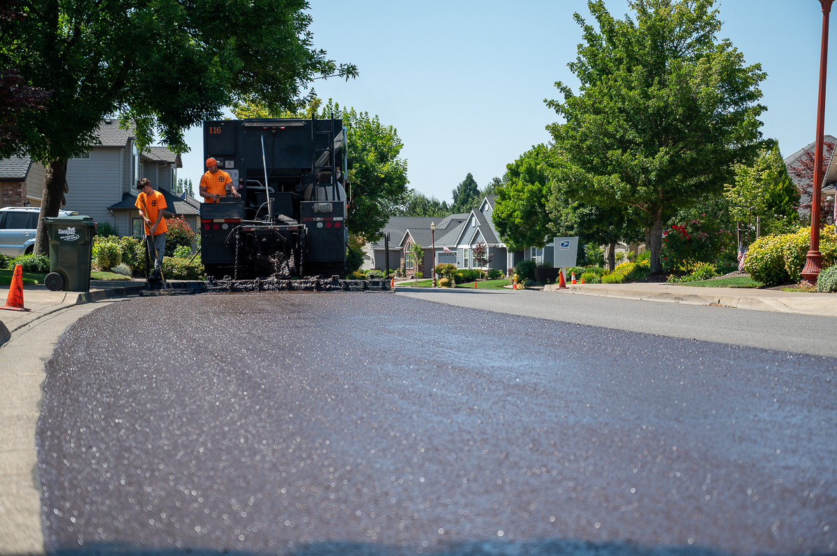 a truck and workers apply a slurry seal to the street